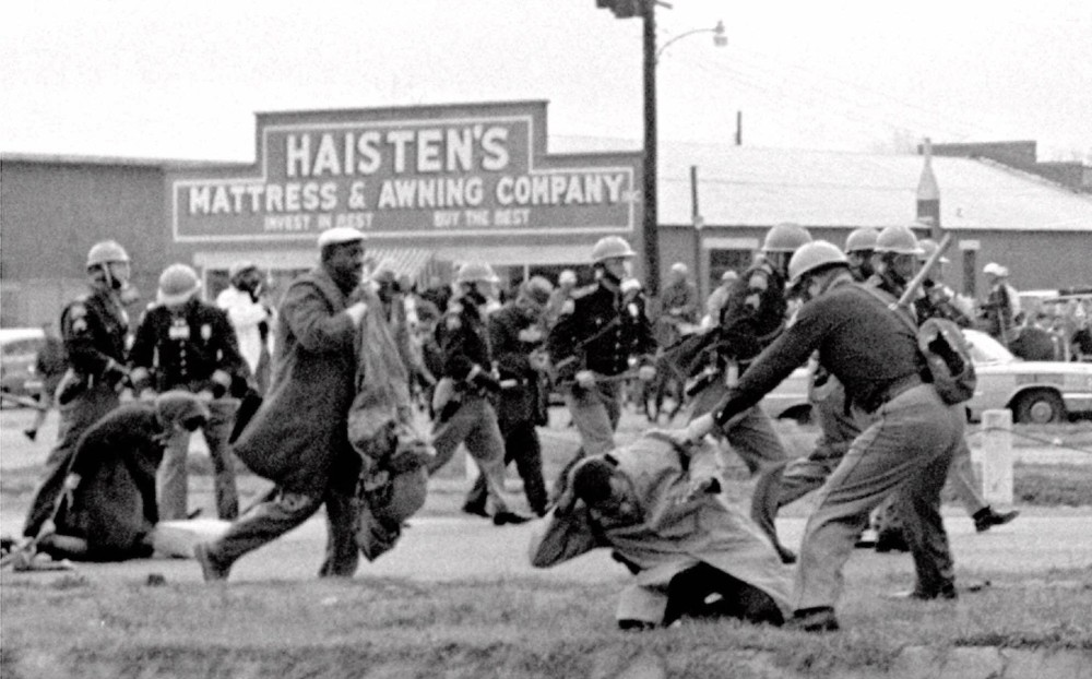 """@@*@@*ADVANCE FOR WEEKEND OF AUG 20–21 @@*@@*FILE @@*@@* Alabama state troopers swing nightsticks to break up the """"Bloody Sunday"""" voting march in Selma, Ala., in this March 7, 1965, file photo. John Lewis, front right, of the Student Non–violent Coordinating Committee is put on the ground by a trooper. The Southern Christian Leadership Conference is inextricably tied to some of the civil rights movement's greatest accomplishments, from the 1963 March on Washington to the """"Bloody Sunday"""" march that led to the Voting Rights Act of 1965. Under the leadership of co–founder Martin Luther King Jr., the organization became a leading voice of a generation galvanized by sit–ins, protests and freedom rides.(AP Photo/File)"""